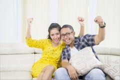 Gelukkige jonge paar het letten op televisie thuis royalty-vrije stock afbeeldingen