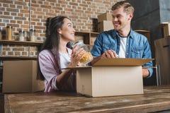 gelukkige jonge paar uitpakkende dozen op keuken terwijl zich het bewegen in stock afbeelding