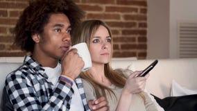 Gelukkige jonge paar veranderende kanalen met de afstandsbediening terwijl thuis het letten van op TV op de bank stock video