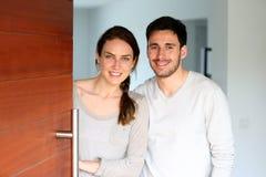 Gelukkige jonge paar welkom hetende gasten in hun huis royalty-vrije stock foto