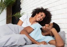 Gelukkige jonge paarontwaken in ochtend in bed stock fotografie