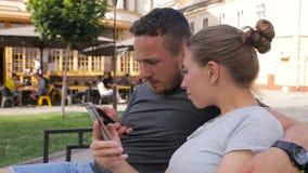 Gelukkige jonge paarzitting op een bank en het gebruiken van slimme telefoon Vrouw en man het letten op video, foto's stock video