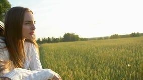 Gelukkige jonge reis die mooie jonge vrouw glimlachen die weg van reis op de tarwegebied van de de zomeraard genieten Het wapen v stock videobeelden
