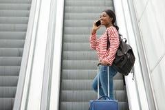 Gelukkige jonge reisvrouw die met mobiele telefoon op roltrap spreken stock afbeeldingen