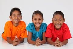 Gelukkige jonge schoolvrienden die op vloer samen liggen Royalty-vrije Stock Afbeeldingen