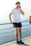 Gelukkige jonge sportman die en zich op mobiele telefoon bevinden spreken stock foto's