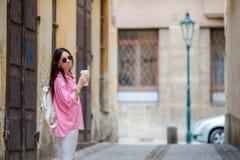 Gelukkige jonge stedelijke vrouw in Europese stad op oude straten Kaukasische toerist die langs de verlaten straten van Europa lo Royalty-vrije Stock Afbeeldingen