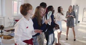 Gelukkige jonge succesvolle zwarte mannelijke manager die dwaas dans het vieren bedrijfssucces met collega's doen bij bureauparti stock video
