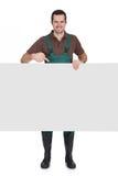 Gelukkige jonge tuinman die lege banner voorstellen Stock Foto