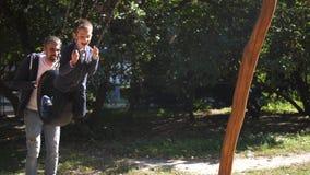 Gelukkige jonge vader en zijn kinderen die op de schommeling bij het park spelen De gelukkige glimlachende vader rolt zijn zoon b stock footage