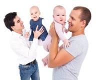 Gelukkige jonge vaders die die met dochters spelen op wit worden geïsoleerd royalty-vrije stock afbeelding