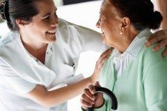 Gelukkige jonge verpleegster met een oude patiënt