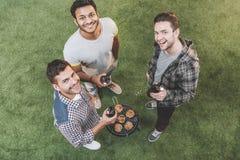 Gelukkige jonge vrienden die bier drinken en barbecue maken Stock Fotografie