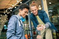 Gelukkige jonge vrienden die nieuw technologisch apparaat met behulp van stock afbeelding