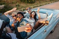 Gelukkige jonge vrienden die selfie met celtelefoon nemen in auto stock afbeeldingen