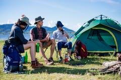 Gelukkige jonge vrienden in kamperende tentpartij die pret hebben samen royalty-vrije stock foto