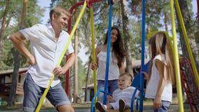 Gelukkige jonge vrolijke familie van vier bij speelplaats` s schommeling stock videobeelden