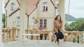 Gelukkige jonge vrouw in beige laag die op schommeling in binnenplaats van Europees kasteel berijden stock videobeelden
