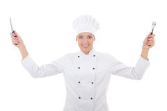 Gelukkige jonge vrouw in chef-kok eenvormig met vork en mes geïsoleerd o Stock Foto's