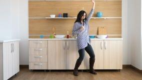 Gelukkige jonge vrouw in de en keuken die dansen zingen stock footage