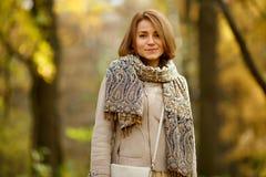 Gelukkige jonge vrouw in de herfstlaag en in tippet in openlucht royalty-vrije stock foto