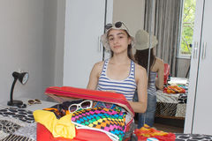 Gelukkige jonge vrouw in de kleurrijke zitting van de de zomeruitrusting dichtbij het rood Stock Fotografie