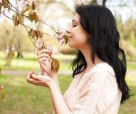 Gelukkige jonge vrouw in de tuin van de lentebloemen royalty-vrije stock foto's