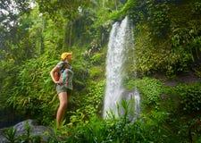 Gelukkige jonge vrouw die backpacker de waterval in wildernissen bekijken stock foto's
