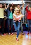 Gelukkige jonge vrouw die bal in kegelenclub werpen Royalty-vrije Stock Foto