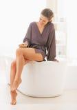 Gelukkige jonge vrouw die been in badkamers masseren royalty-vrije stock fotografie