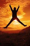 Gelukkige jonge vrouw die bij de zonsondergang springen Stock Afbeeldingen