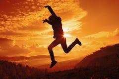 Gelukkige jonge vrouw die bij de zonsondergang springen Royalty-vrije Stock Foto