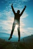 Gelukkige jonge vrouw die bij de zonsondergang springen Stock Afbeelding