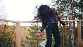 Gelukkige jonge vrouw die bij hoge hoogte en het glimlachen dansen Langzame Motie stock video