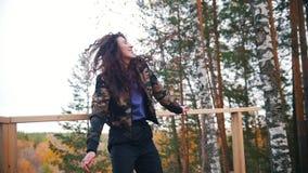 Gelukkige jonge vrouw die bij hoge hoogte en het glimlachen dansen Vliegend krullend haar Bos stock footage