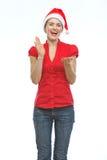 Gelukkige jonge vrouw die in de hoed van Kerstmis handen slaat stock afbeeldingen