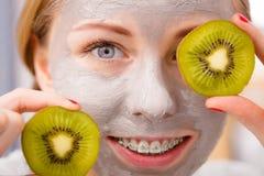 Gelukkige jonge vrouw die de holdingskiwi hebben van het gezichtsmasker royalty-vrije stock afbeelding
