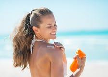 Gelukkige jonge vrouw die de room van het zonscherm toepassen stock foto