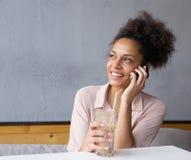 Gelukkige jonge vrouw die door mobiele telefoon roepen Stock Afbeelding