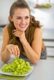 Gelukkige jonge vrouw die druif in keuken eten Stock Afbeeldingen
