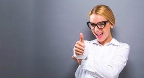 Gelukkige jonge vrouw die duimen geven Royalty-vrije Stock Foto