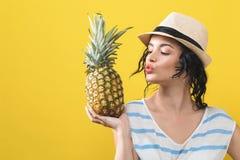 Gelukkige jonge vrouw die een ananas houden royalty-vrije stock foto's