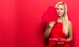 Gelukkige jonge vrouw die een grote doos van de hartgift houden Stock Afbeelding