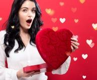 Gelukkige jonge vrouw die een grote doos van de hartgift houden Stock Foto's