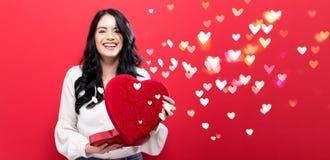 Gelukkige jonge vrouw die een grote doos van de hartgift houden Royalty-vrije Stock Fotografie