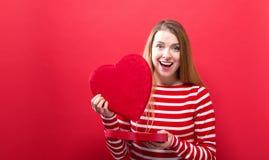 Gelukkige jonge vrouw die een grote doos van de hartgift houden Stock Foto