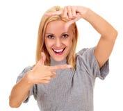 Gelukkige jonge vrouw die een kader met haar vingers creëren stock foto's