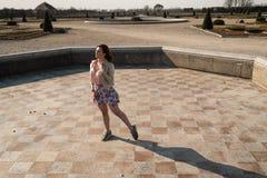 Gelukkige jonge vrouw die in een lege fontein danst die een kleurrijke rok draagt stock foto