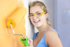 Gelukkige jonge vrouw die een muur schildert Royalty-vrije Stock Foto's