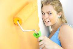 Gelukkige jonge vrouw die een muur schildert Stock Fotografie